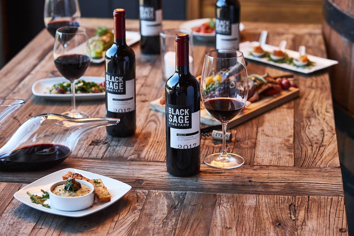 lifestyle image of red wine, fine food and decanting red wine by kelowna photographer on location at winery